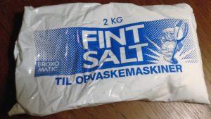 """Illustration af hvid pose med filtersalt og blå skrift med teksten: """"Fint salt til opvaskemaskinen""""."""