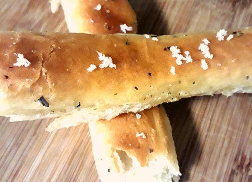 Færdiglavet brødstænger på skærebræt med salt drysset henover